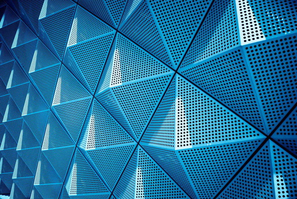 Abstract image of a metal looking wall made of raised pyramid panels in blue tones