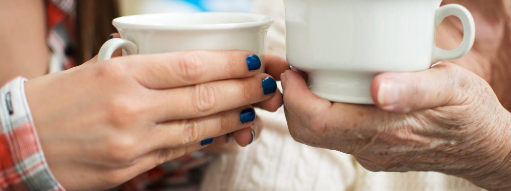 Close up of two people holding white tea cups, on the left a younger person and on the right an older person