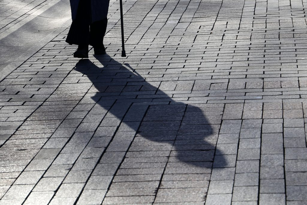 Grey brick path with retired adult's shadow in middle and silhouette of their feet, lower legs and walking stick