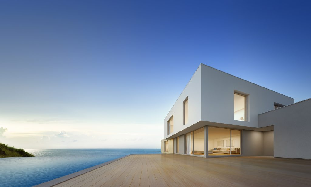 Modern home with glass windows and wooden patio area, infinity pool, sea and sky in background in early evening