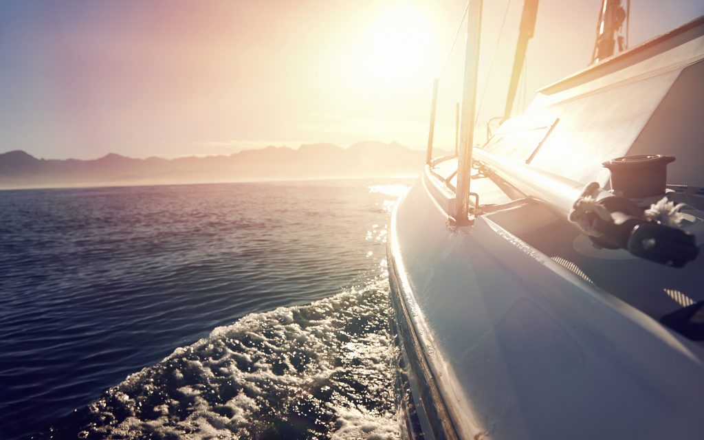 Side view of a sailing boat, sailing into the horizon and the sun is setting.