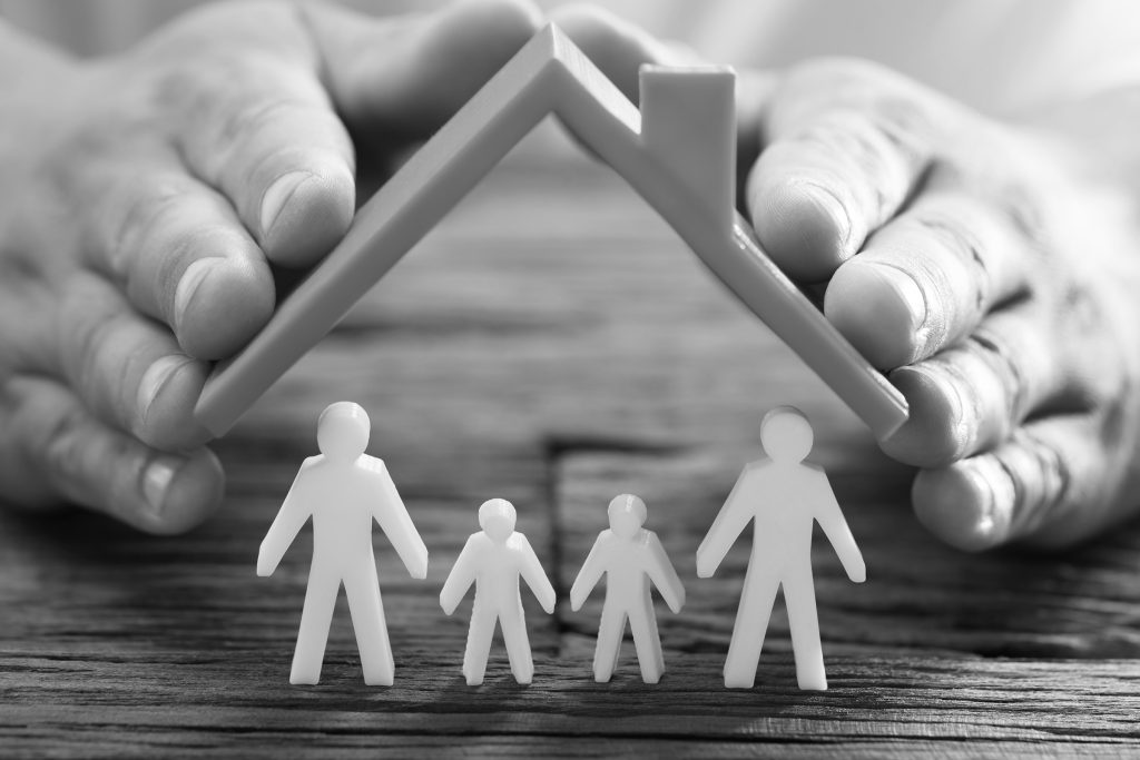Man holding plastic toy. A plastic family are underneath the roof and standing on wooden table