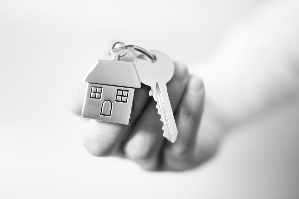 Hand holding a key ring with a house trinket and door key on it, nothing in the background