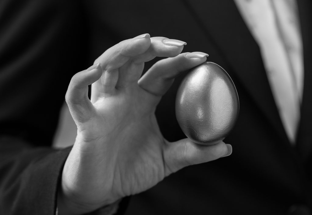 Close up of a female's hand holding a gold egg, in black and white