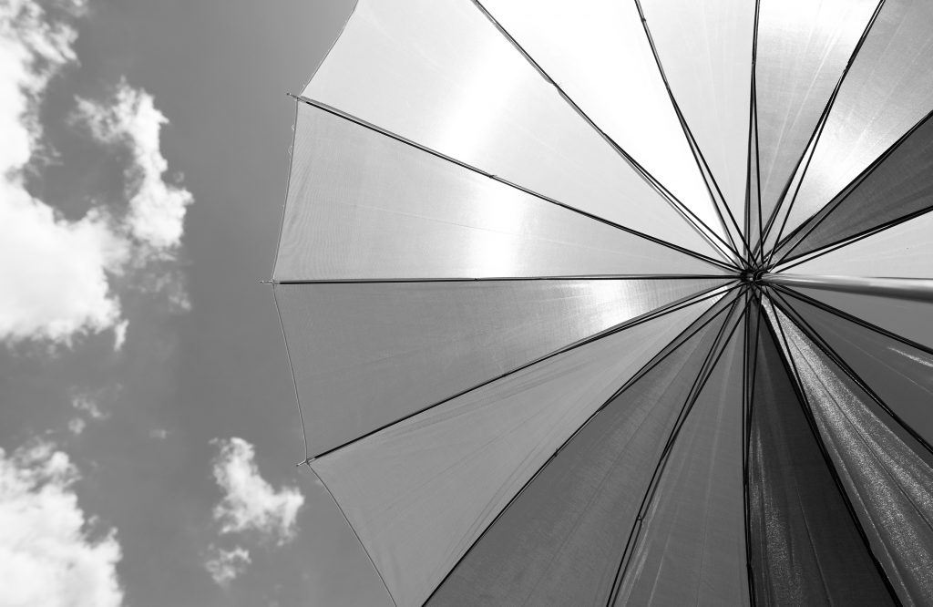 Underside of a large protective umbrella with the sky in the background