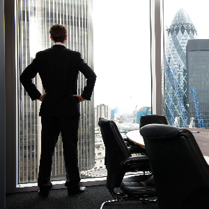 Man in corner of office looking at the City, Gherkin in skyline. Wooden table with leather chairs in office.