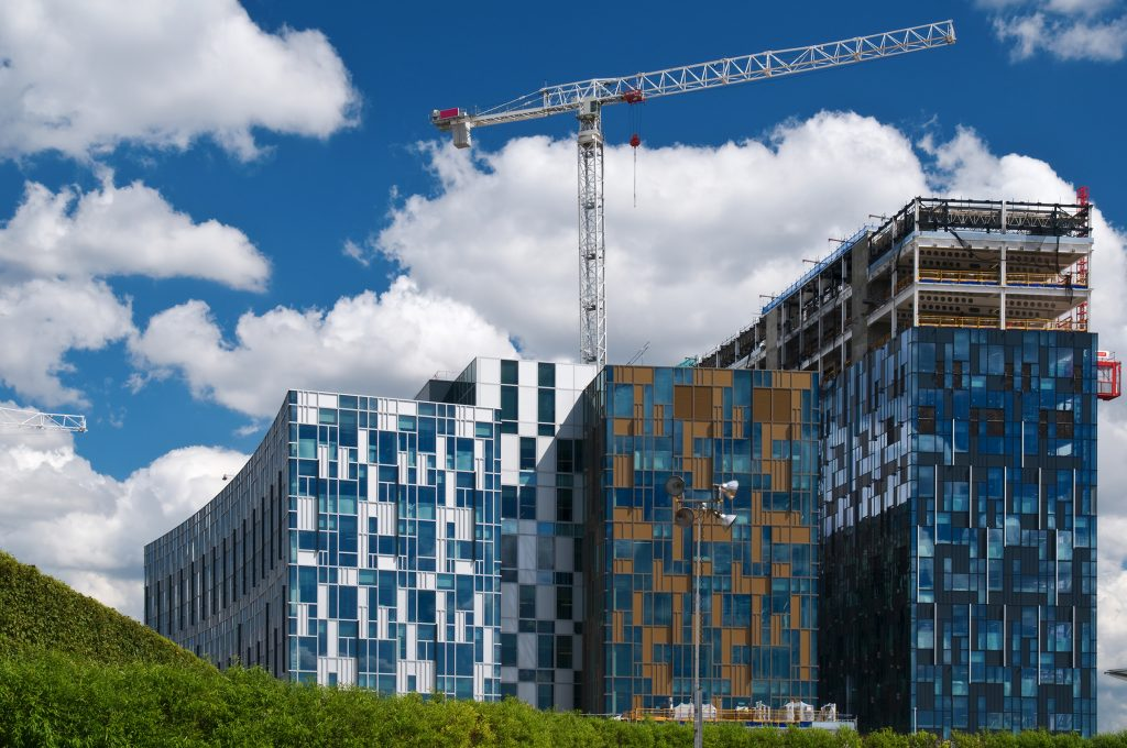 Close up of modern glass buildings being built, with crane in background and blue sky and white clouds.