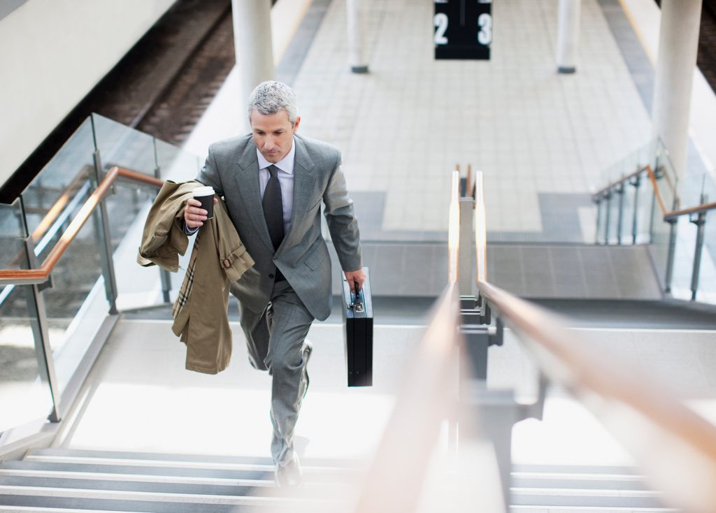 A businessman carrying a briefcase, coat and coffee walking up train station platform stairs
