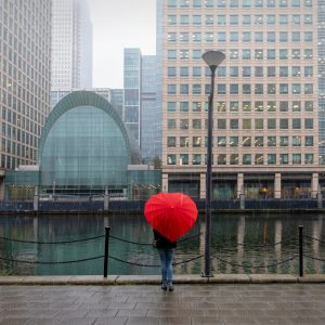 Lady standing and holding a red protective umbrella across from buildings on Docklands.