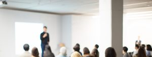 Blurred image of a man giving a talk in a conference room with people sitting listening