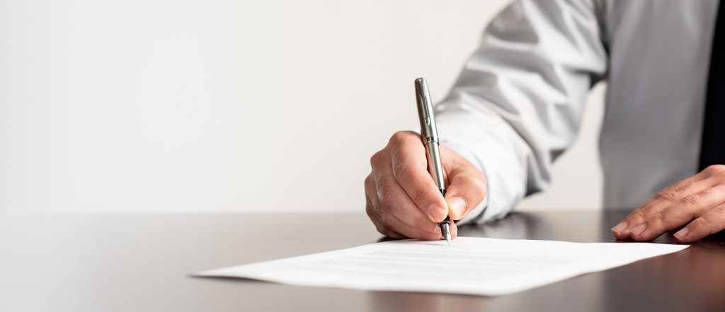 Close up of a businessman's hand signing a document with a fountain pen