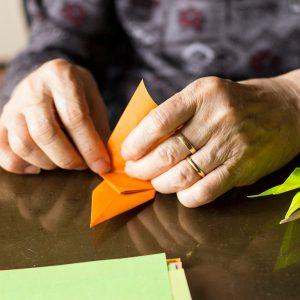 Older lady's hands folding coloured paper