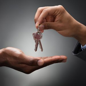 Hand holding a set of door keys with another hand cupped underneath ready to catch them.