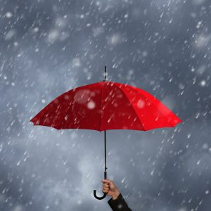 - An image of a hand holding a red umbrella for protection with grey sky and rain falling