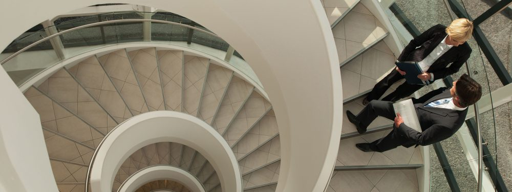 Spiral staircase which looks like a snail shell and a businesswoman and businessman chatting