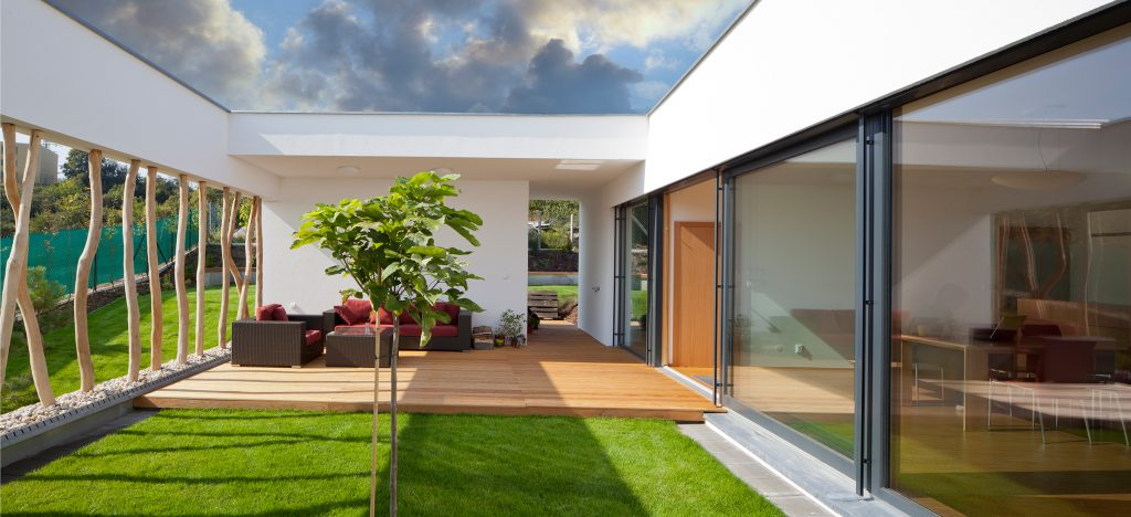 Garden room with grass, decking and outdoor corner seating area, large glass window and tree trunks.