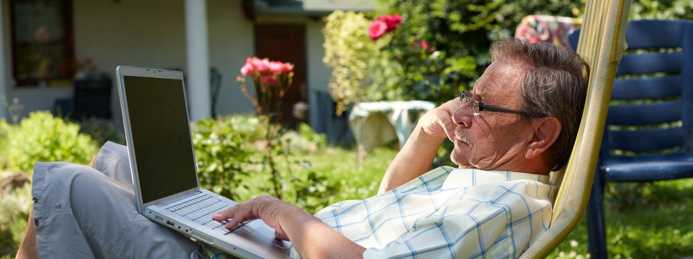Retired man sitting in a garden deck chair working on his laptop with garden and house in background