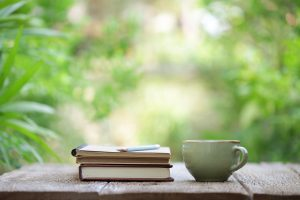 Close up of a tea cup, a stack of three note books and two pencils on top of a wooden table and a blurred garden