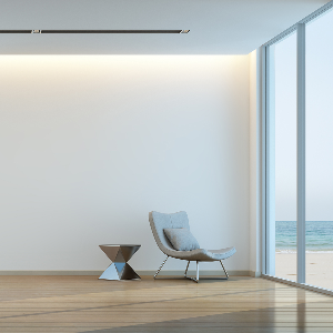 Interior view of a modern minimalist home with chair and small coffee table, few possessions.