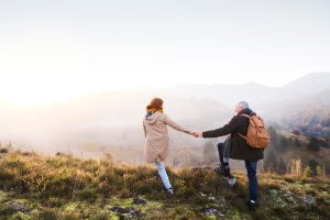 Older couple walking on the top of a mountain holding hands on a dusky autumn day
