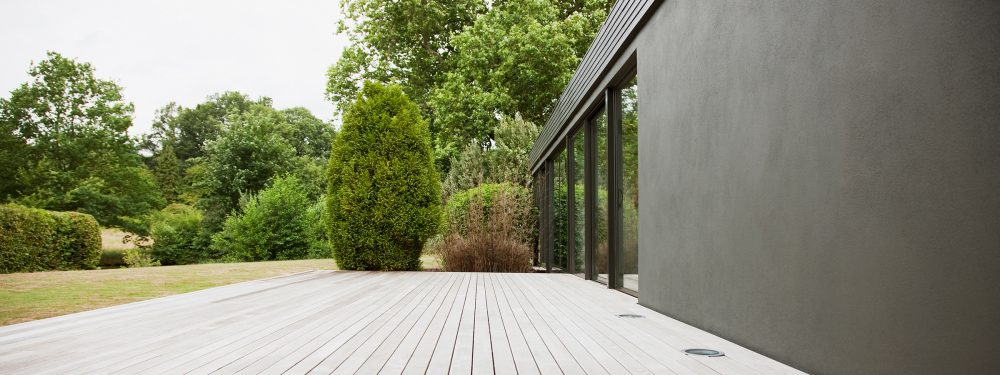 Exterior view of a modern home with glass patio doors. Decking, lawn, bushes and trees in background