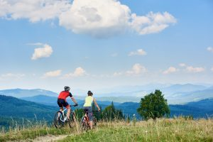 Male and female cycling in the countryside on a sunny day with clear blue skies. Mountains in the background.