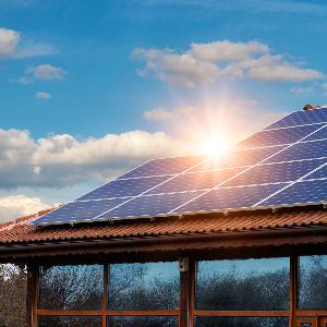 View of a building roof with energy saving solar panels, sunshine beaming.