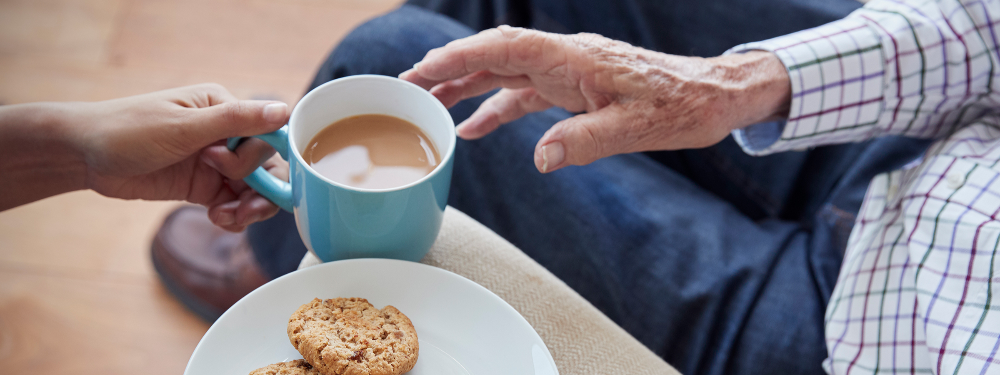 Close up bird's eye view of caring lady passing a cup of tea and plate of biscuits to an older man