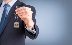 Young man's hand holding a front door key with a house key ring hanging