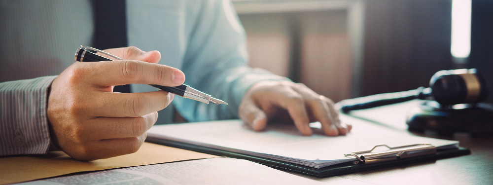 Close up image of a businessman holding a fountain pen getting ready to sign a Will.