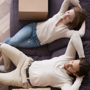 Young couple sitting on a sofa relaxing, with house moving boxes next to them and on the floor