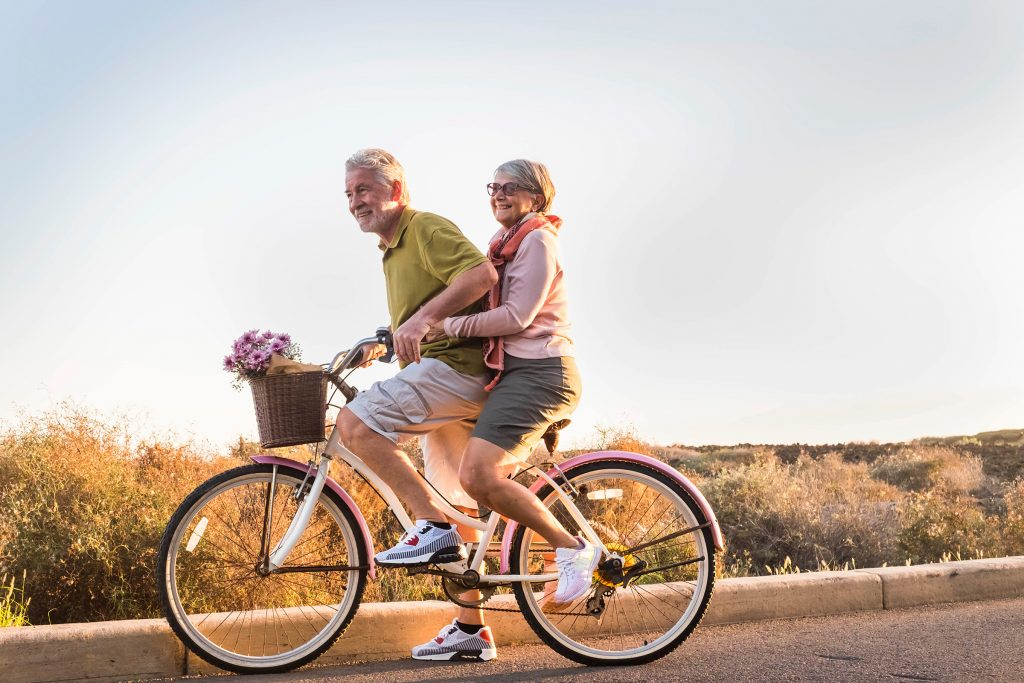 An older couple (female and male) smiling riding a bicycle along a road with countryside behind them