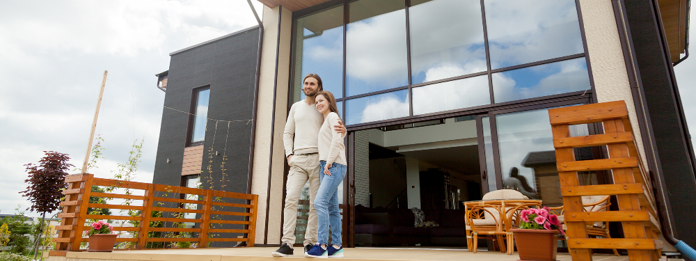 A young couple standing outside a modern house looking out at the view