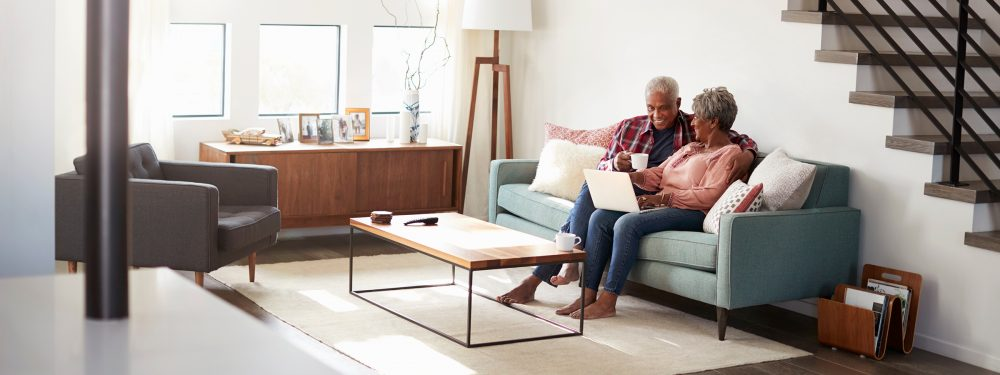 A retired couple sitting on a green sofa in a modern living room looking at a laptop and drinking tea