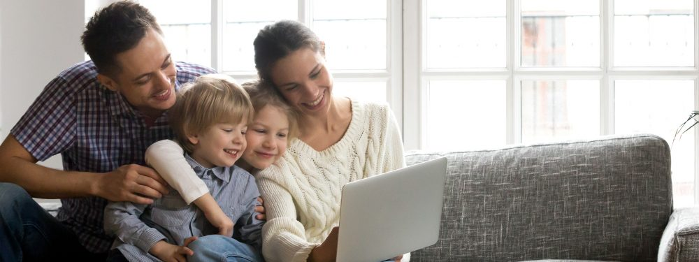 A family of Mum, Dad, brother and sister sat on a sofa looking at a laptop
