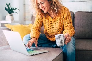 A woman sitting on a grey sofa looking at a laptop with a patterned mug in her hand
