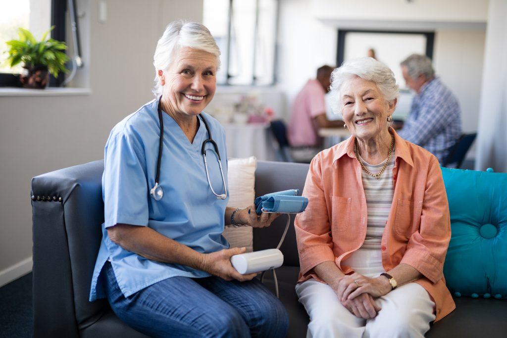 An older lady sitting on a sofa with a senior caring nurse about to take her blood pressure