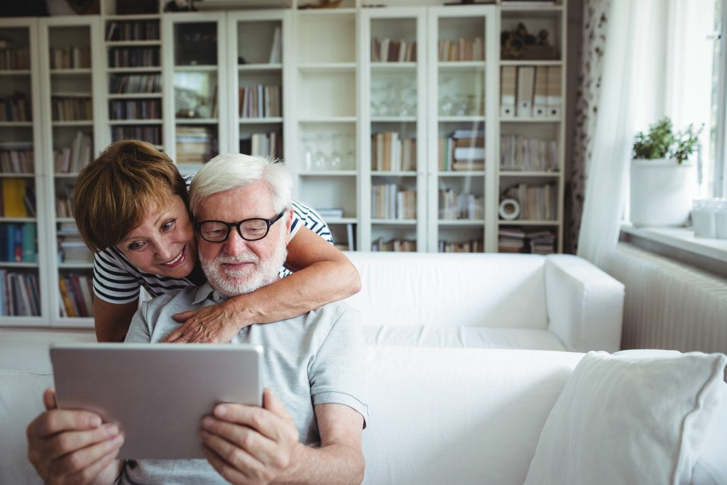 An older retired female with her arms around her husband who is sitting on a sofa, looking at a tablet.