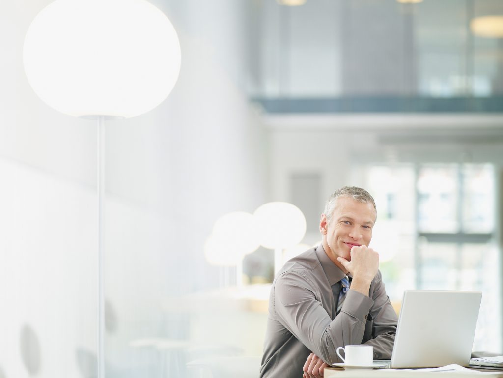 Smiling businessman sitting in a bright office with laptop, cup and saucer and paperwork on the table.
