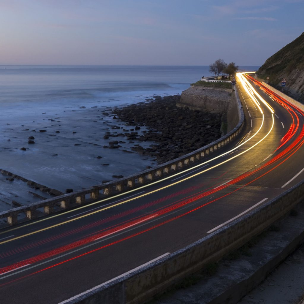 Landscape image of a coastal road at night. Taken with a long exposure so there are red and white shafts of light casts coming from the cars