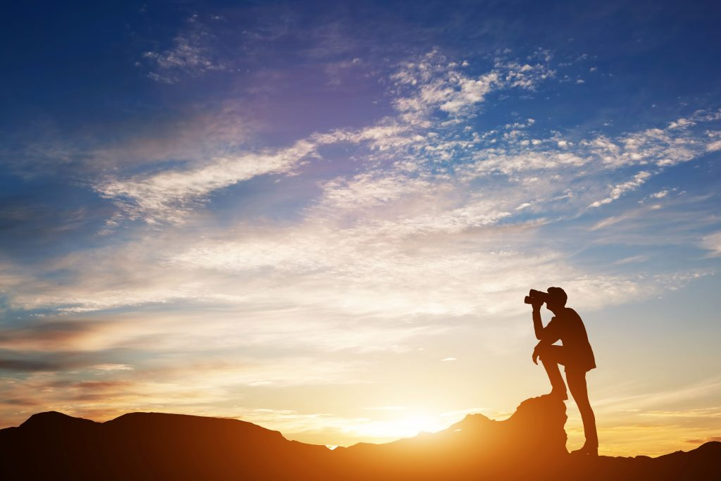 Man standing at the top of a mountain looking through looking forward through binoculars