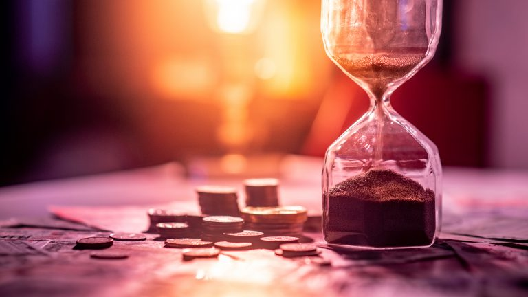 Sand running through hourglass on table with money showing time passing for financial investment within a deadline