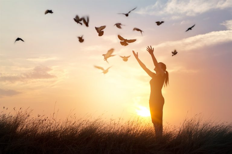 Woman investing in a peaceful moment, enjoying birds flying in the sunrise early in the morning