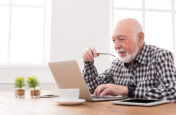 Man of retirement age looking on his laptop at his pension