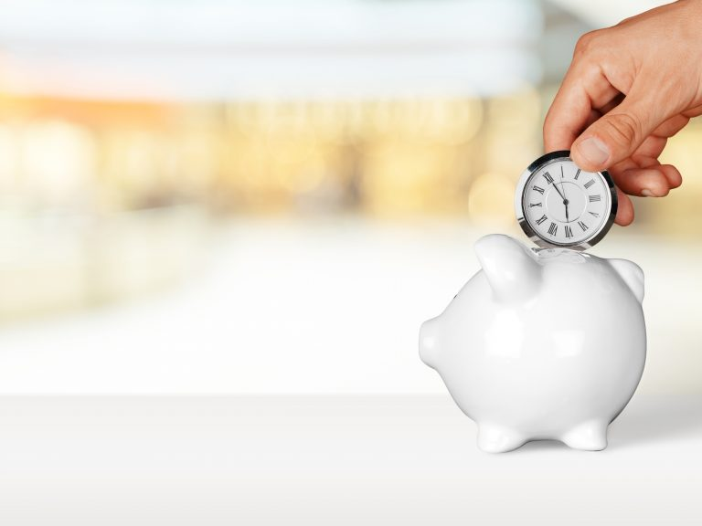 Hand holding a pocket watch above a white piggy bank, time pays off for early bird ISA investors