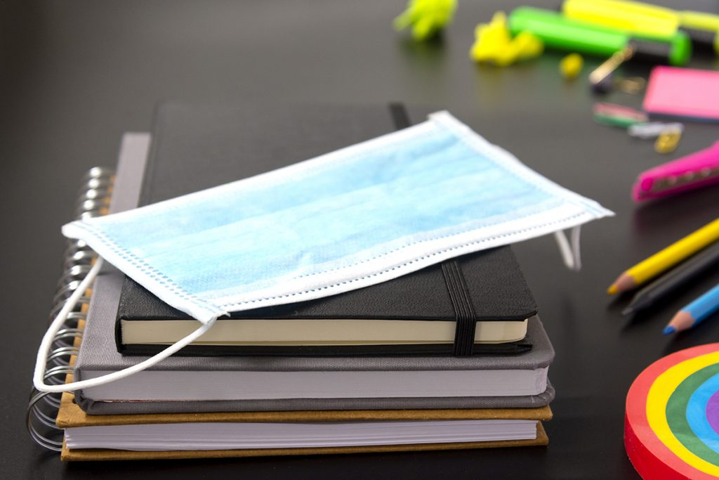 Stack of school books and pens on a desk with a facemask placed on top, adhering to Covid19 safety measures.