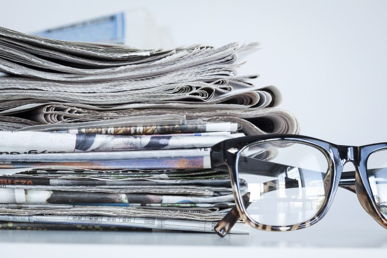 Stack of newspapers reporting on unclaimed pension pots an dividend drought