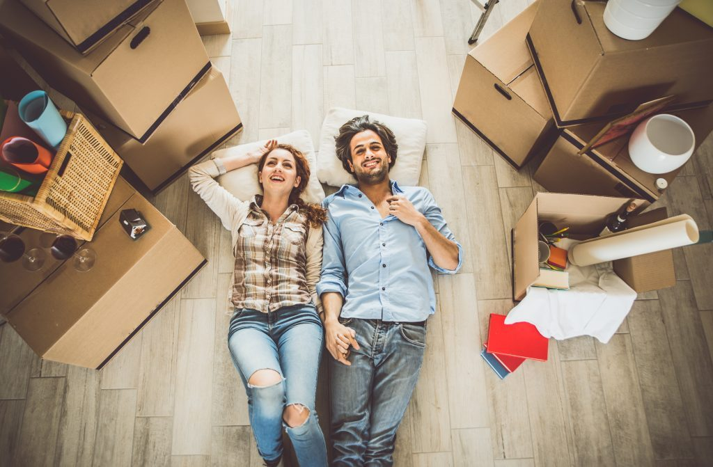 A couple laying on the floor holding hands with moving boxes all around them, post lockdown trends ruling the property market