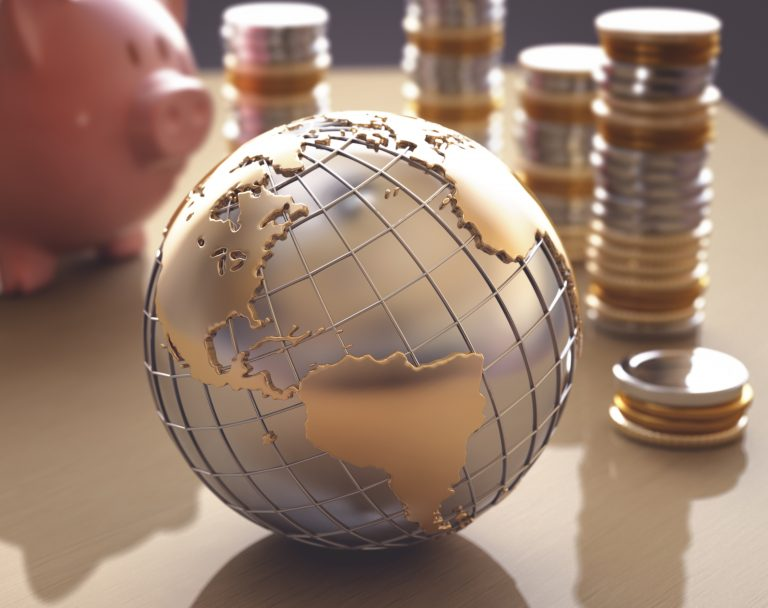 World ornament with stacks coins and piggy bank in the background, where now for the global economy