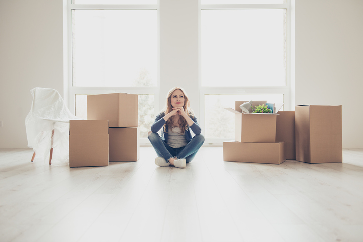 Happy lady sitting in an empty living room with moving boxes around her, mortgage markets recovery